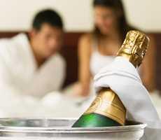 Deux amoureux dans un lit qui boivent du champagne au Impéria Hôtel et suites