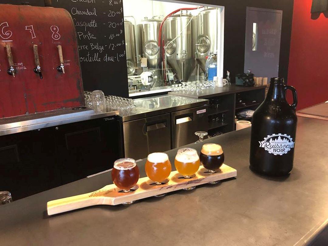 Planche de bois utilisée comme socle pour quatre bières différentes.