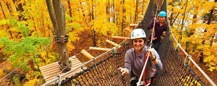 Deux filles dans les parcours dans les arbres à Arbraska en automne