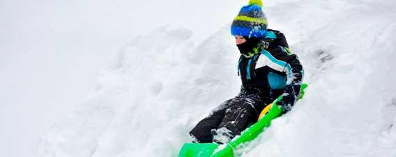 Garçon qui glisse sur la neige