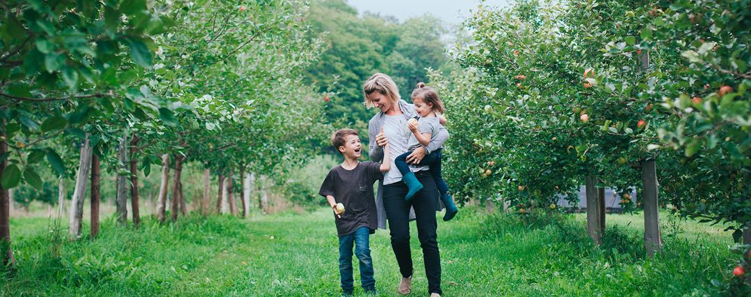Family walking in the orchard at Qui sème récolte