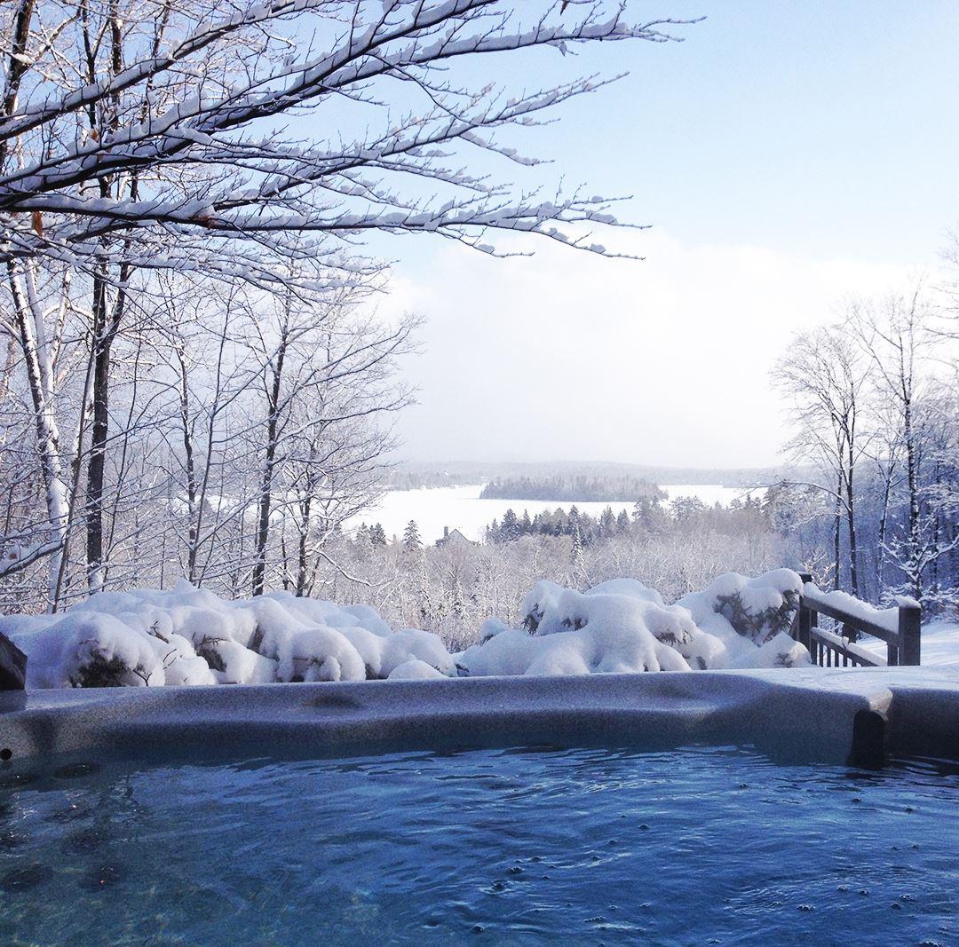 Spa avec vue sur le lac en hiver Chalets Évasion