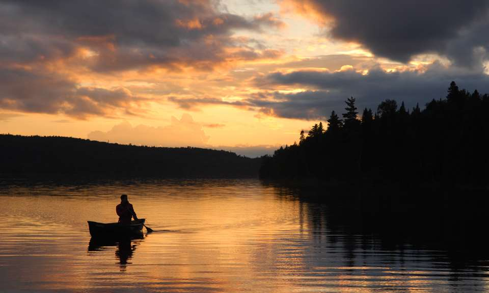 A man on a canoe at Parc national du Mont-Tremblant during a sunset