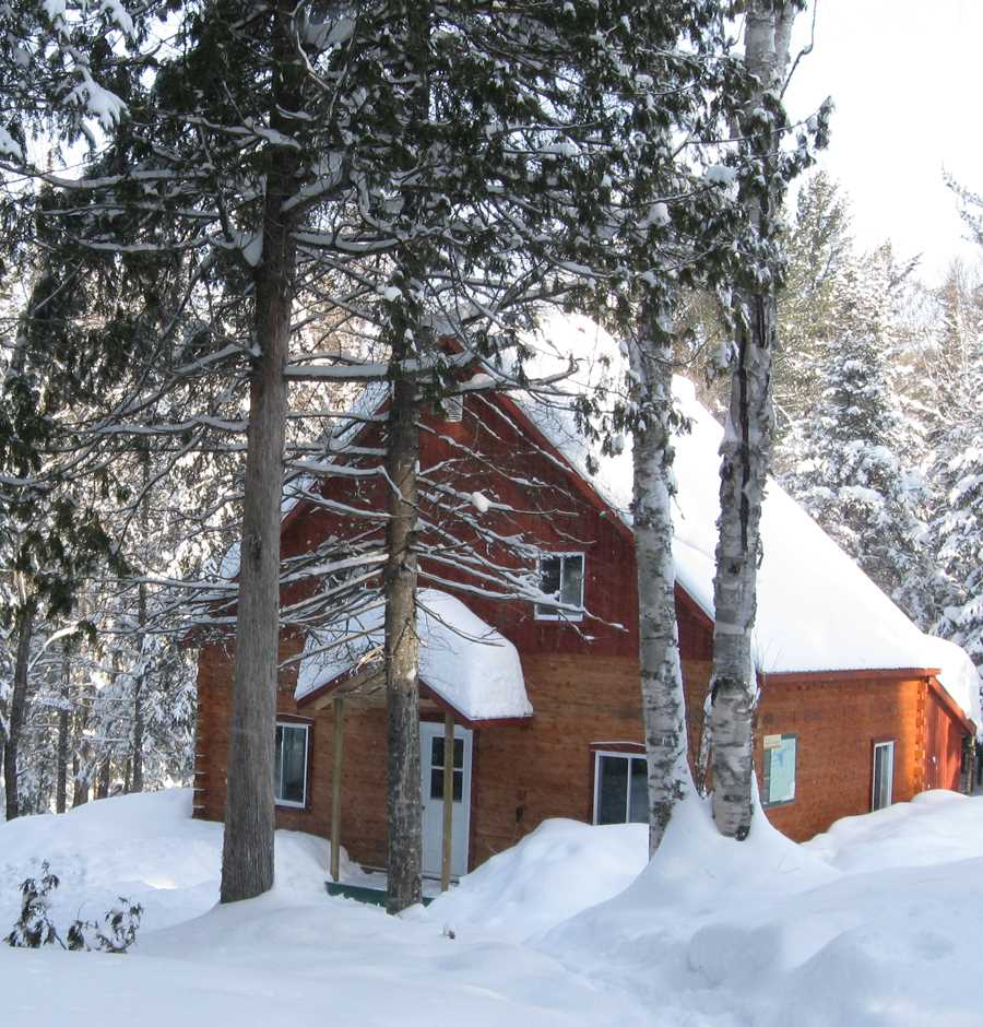 A cottage during winter at the Sentier National in the forest
