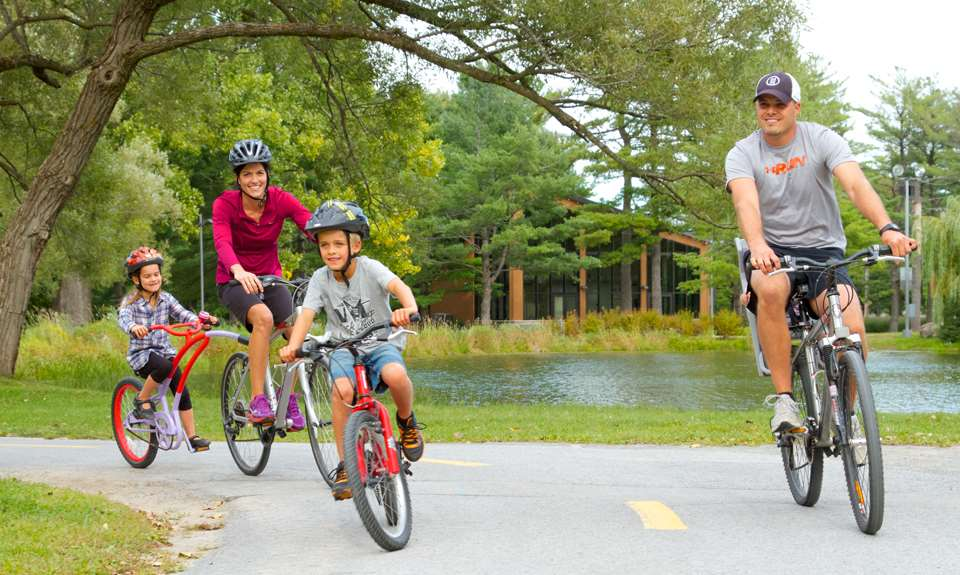 A happy family ride a bicycle in the Parc du Grand-Coteau