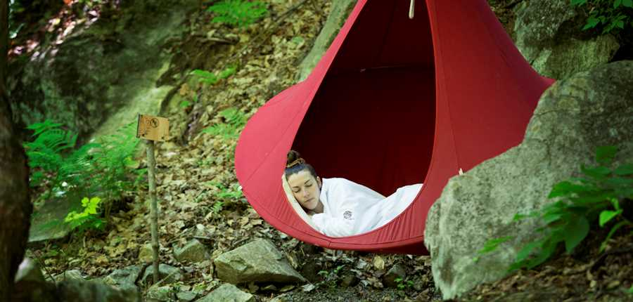 Woman relaxing in a hammoc at La Source Bains Nordiques
