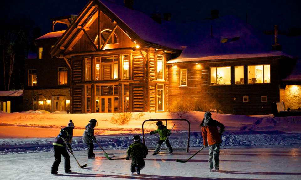 Kids playing ice hockey in front of Auberge du Lac taureau during winter