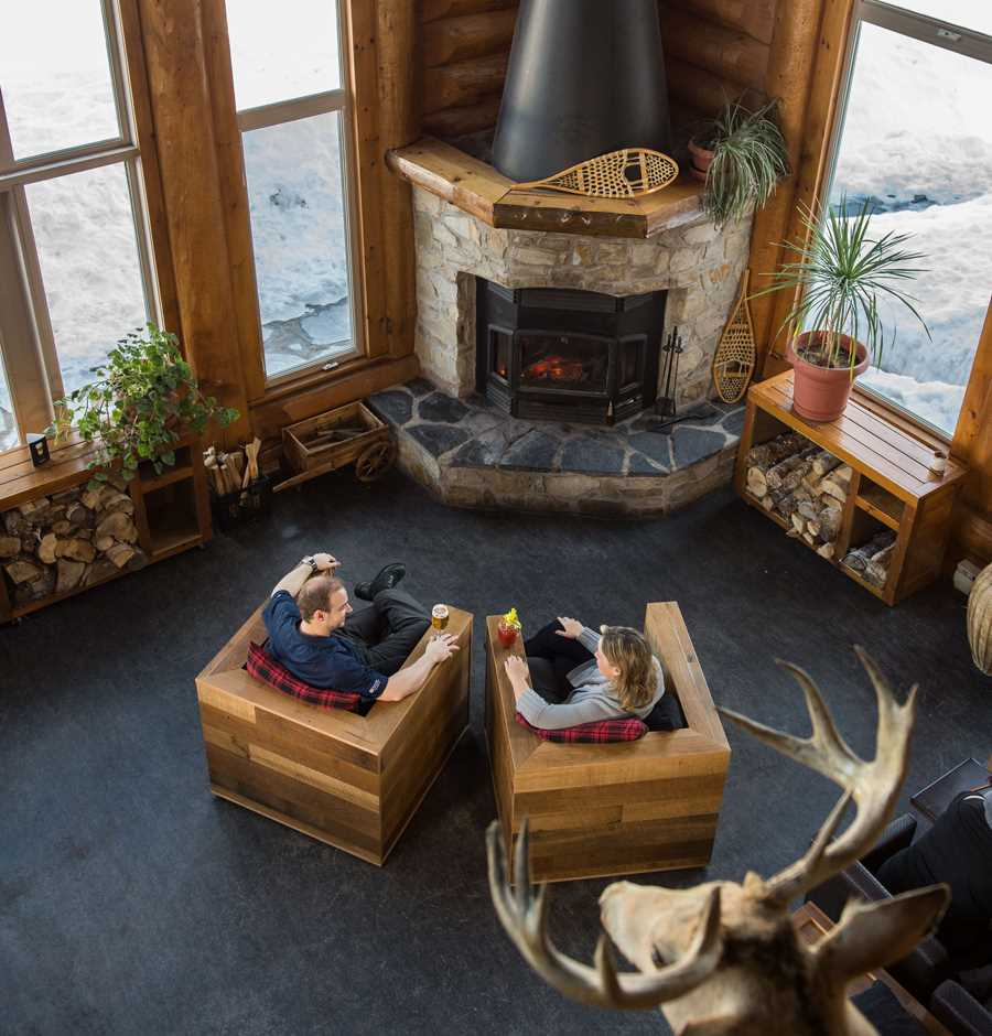 Couple relaxing in front of a fireplace at Auberge du Lac Taureau
