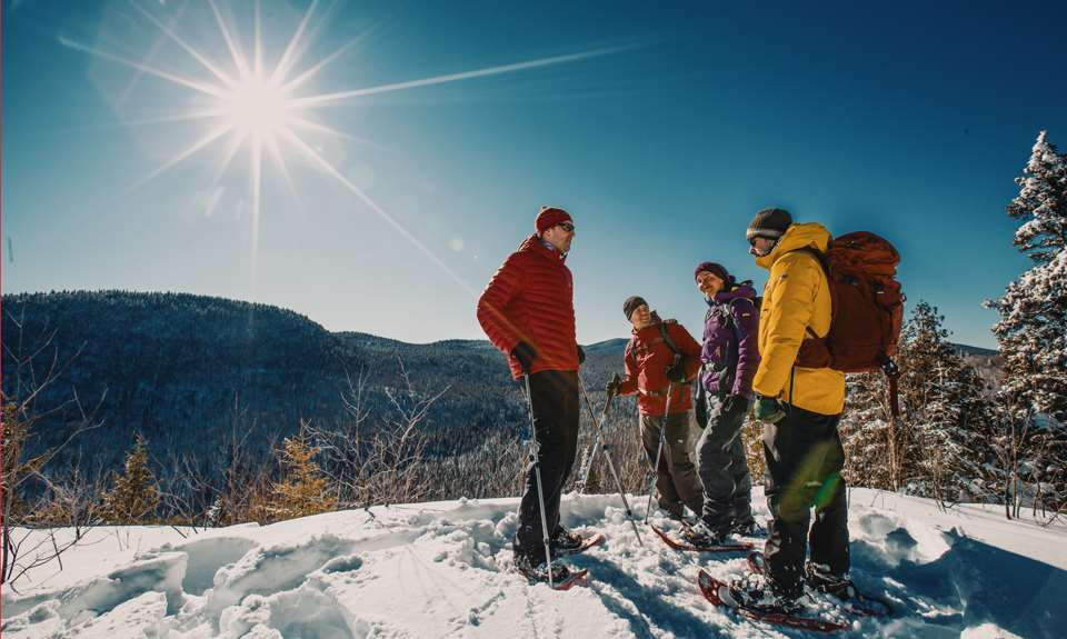 A group snowshoeing on top of a mountain at the Parc national du Mont-Tremblant