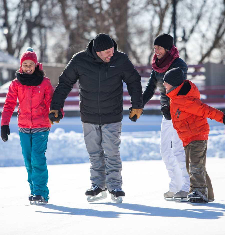 Family ice-skating together at Île-des-Moulins
