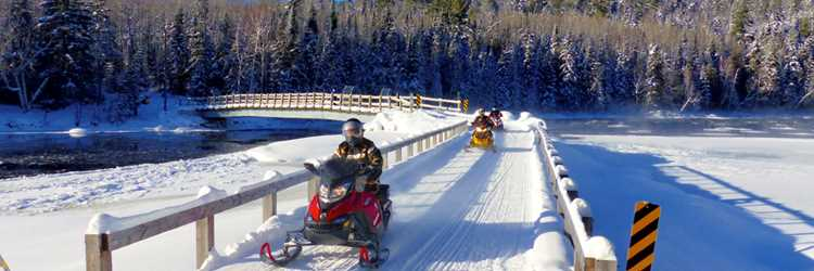 People doing snowmobile during winter on the Pont Matawin