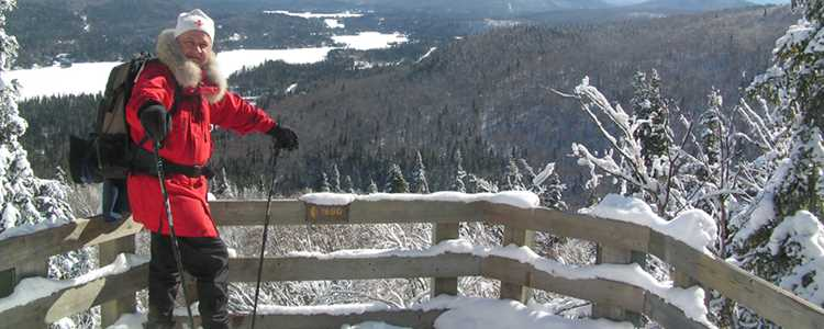 Un homme qui fait de la raquette au sommet du sentier l'Envol au parc national du Mont-Tremblant