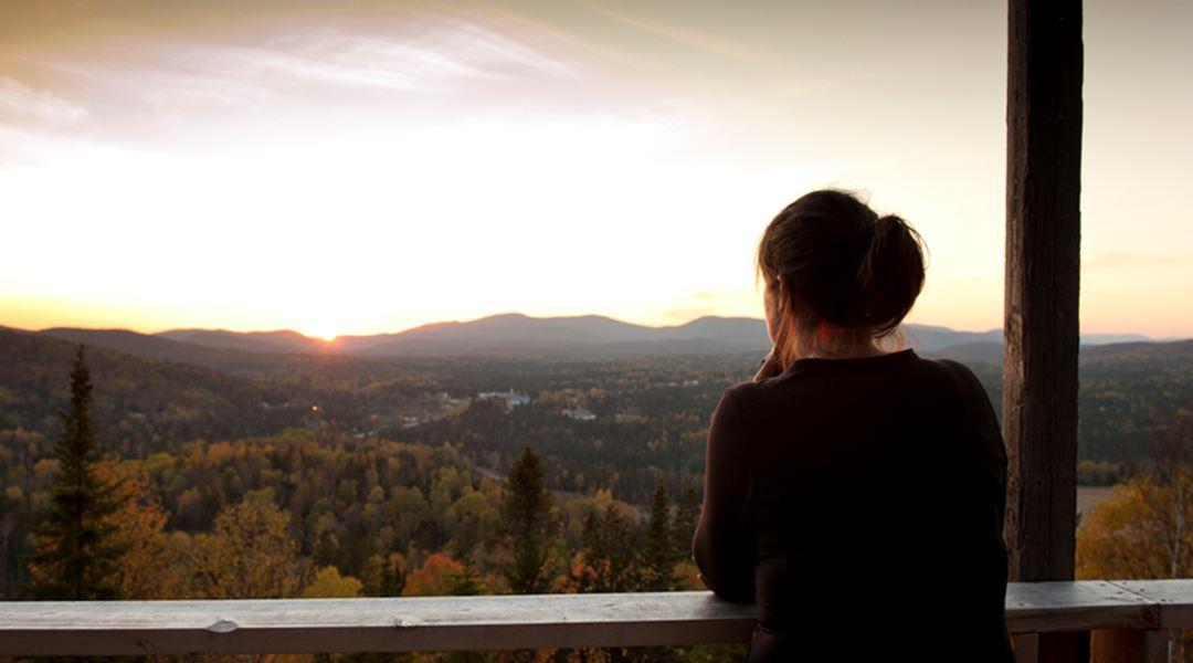 Une femme au sommet du sentier belvédère de la Croix avec une vue des montagnes
