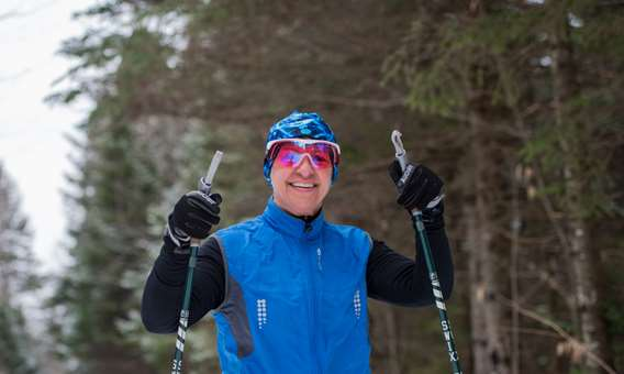 Happy woman cross-country skiing at Ski Montagne Coupée
