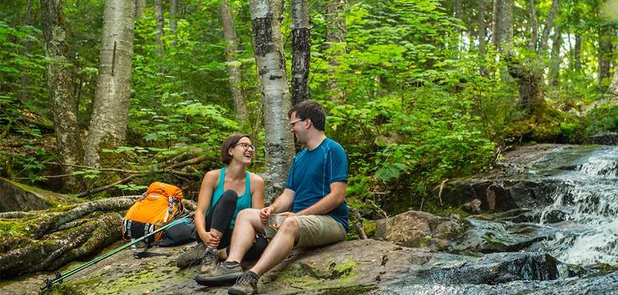 Couple taking a break near a stream