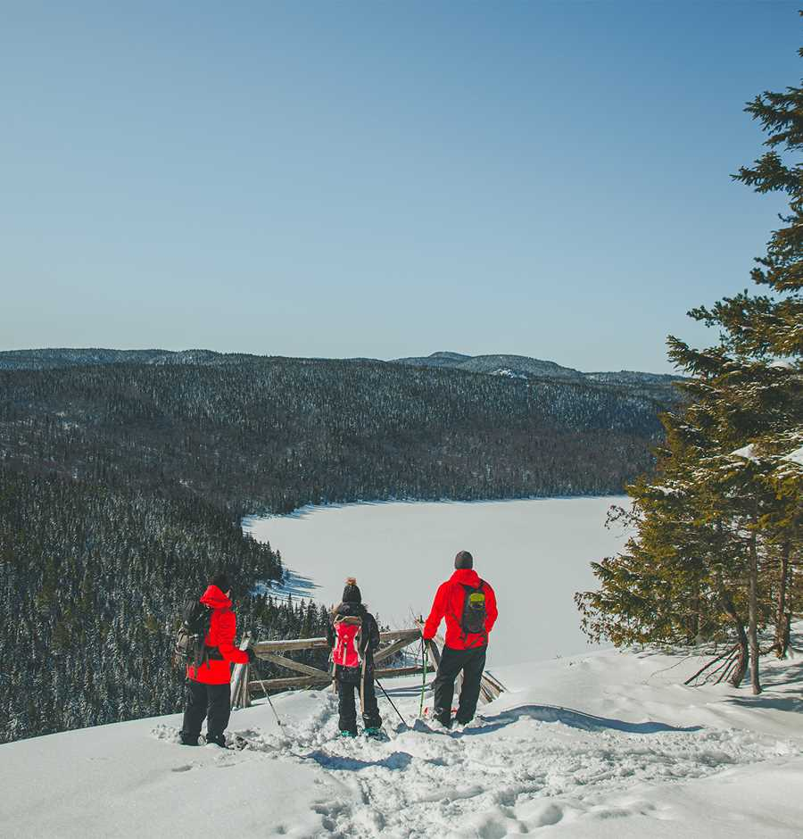 3 snowshoers with a view of Lake Rémy