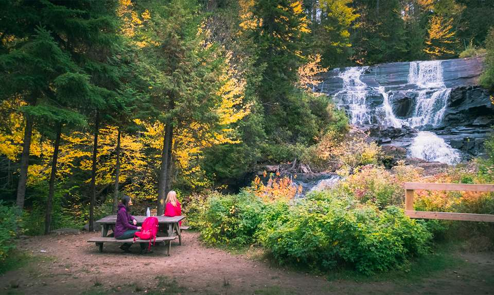 Two people watching a waterfall